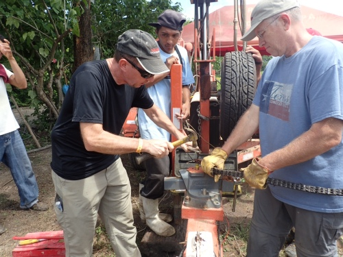 Don Davis and Mike Aronson repairing broken chain on drill rig.